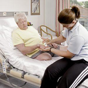 Behandelaar start met compressietherapie bij patiënt
