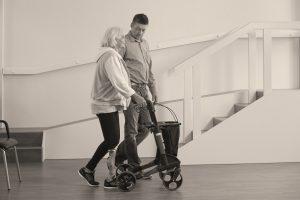 Mevrouw loopt met knieprothese Kenevo van Ottobock en met rollator