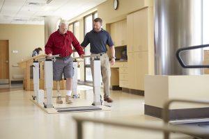 Man leert lopen met een prothese aan loopbrug
