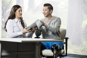 Man met beenamputatie zit aan tafel bij instrumentmaker
