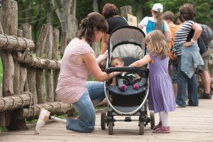 Vrouw met prothesevoet Trias van Ottobock knielt bij kinderwagen van haar kind