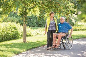 Een man in rolstoel is samen met zijn vrouw buiten voor een ommetje