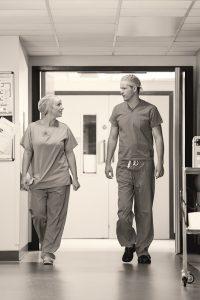 Twee medewerkers van het ziekenhuis lopen door de gang terwijl ze met elkaar in gesprek zijn