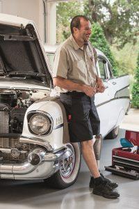 Man bij bovenbeenprothese staat bij auto