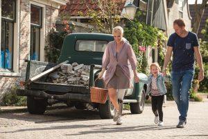 Foto van stel met kind wandelend door de straat