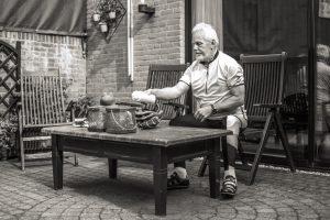 Ervaringsdeskundige Peter zit aan tafel in sportkleding